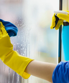 A cleaner wearing yellow gloves uses a spray bottle and a blue cloth to clean a mirror.