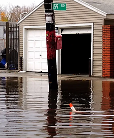 A flooded home is seen from a flooded street, presumably after a storm.