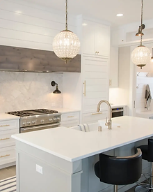 A clean white, grey, and brown household kitchen with gold and crystal ornamental lights.