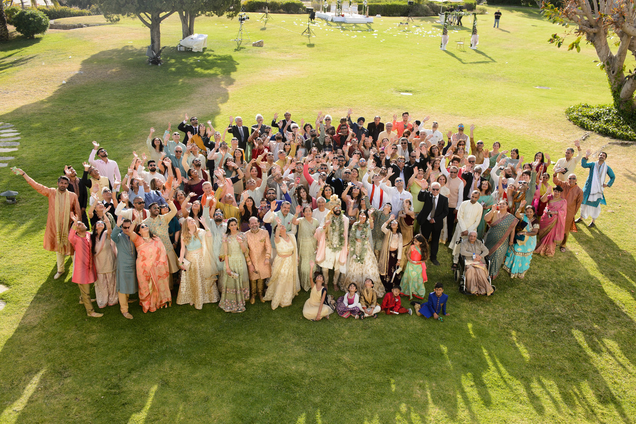 Asian bride and groom with all their guests at their Hindu wedding ceremony in the Algarve, Portugal at Pestana Alvor Praia