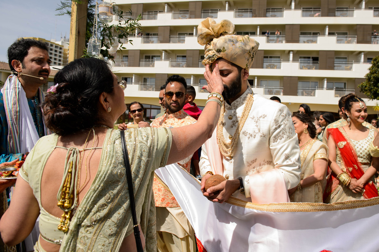 Asian groom being blessed by mother of the bride at his Hindu wedding ceremony in Algarve, Portugal