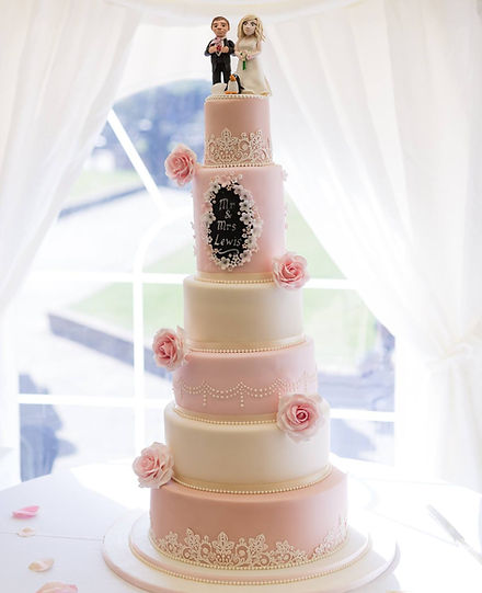 A wedding cake with handmade toppers and roses.