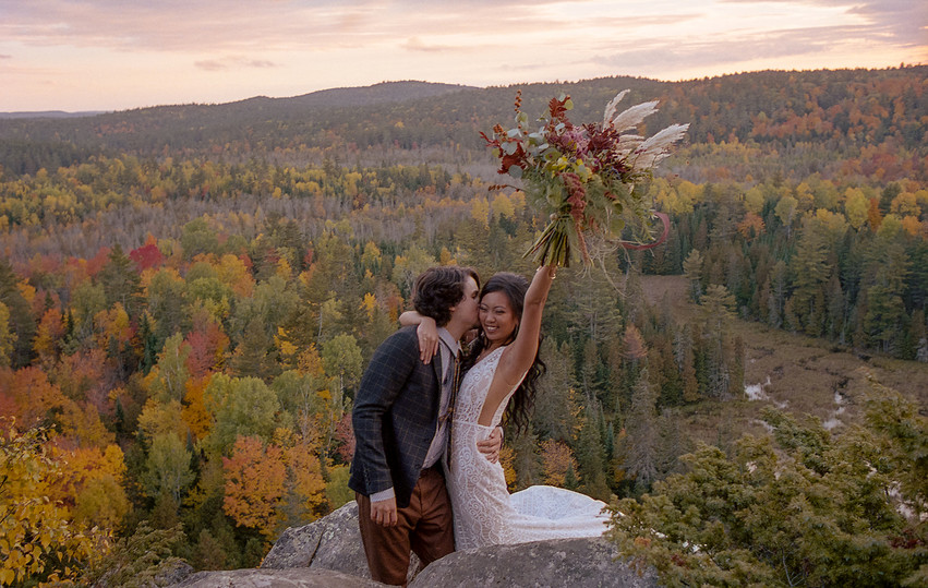 Bride and Groom on a cliff overlooking autumn trees