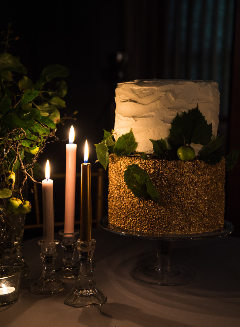 Wedding cake with gold, leaves and candles