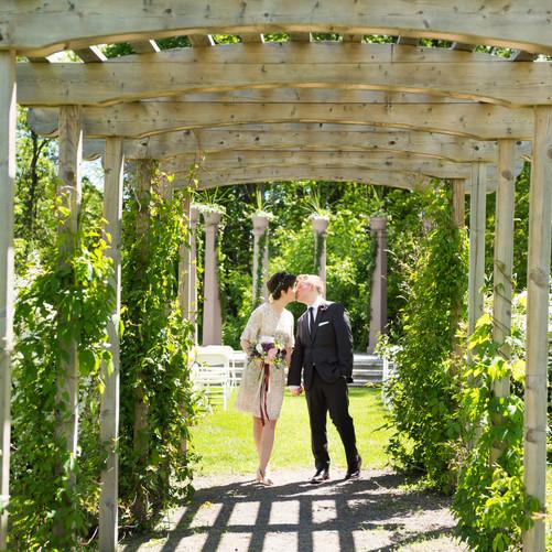 Bride and Groom kissing under a garden arbor