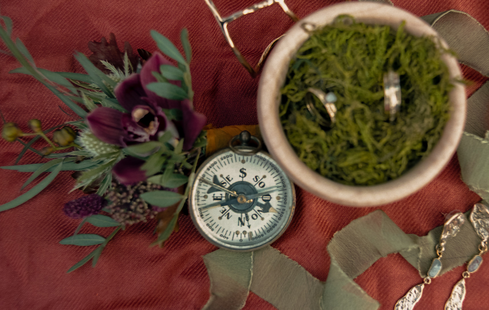 Wedding rings, jewelry, boutonierrre, and ribbon with compass