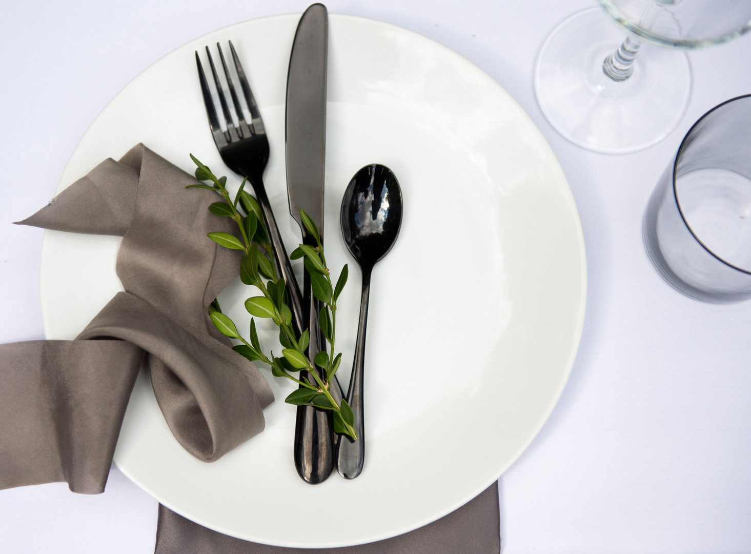 Wedding reception table setting with ribbon and black flatware