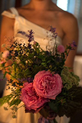 Bride with one-shouldered wedding dress and bouquet of garden roses
