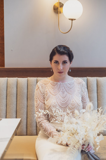 Bride wearing beaded pearl wedding dress with dried flower bouquet