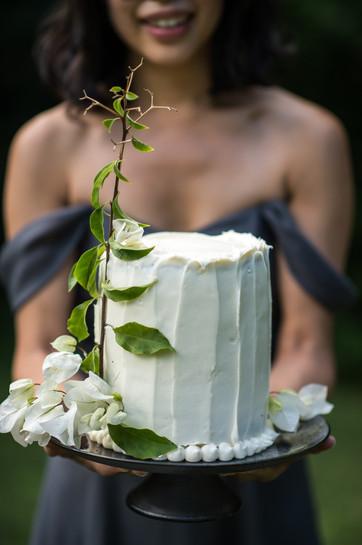Bridesmaid with tall white wedding cake