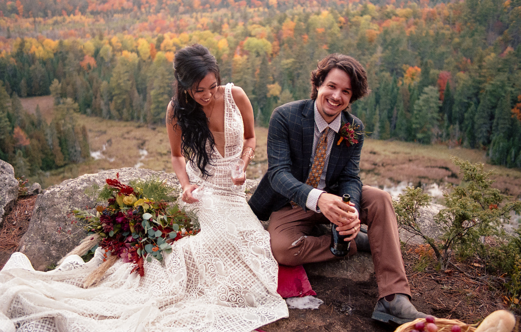 Bride and Groom opening champagne on a cliff
