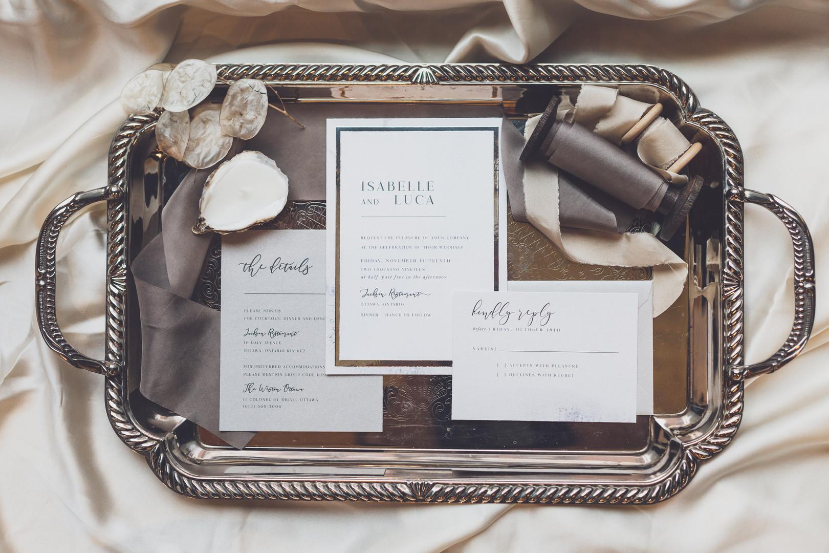 Wedding invitation with silk ribbon on a silver tray