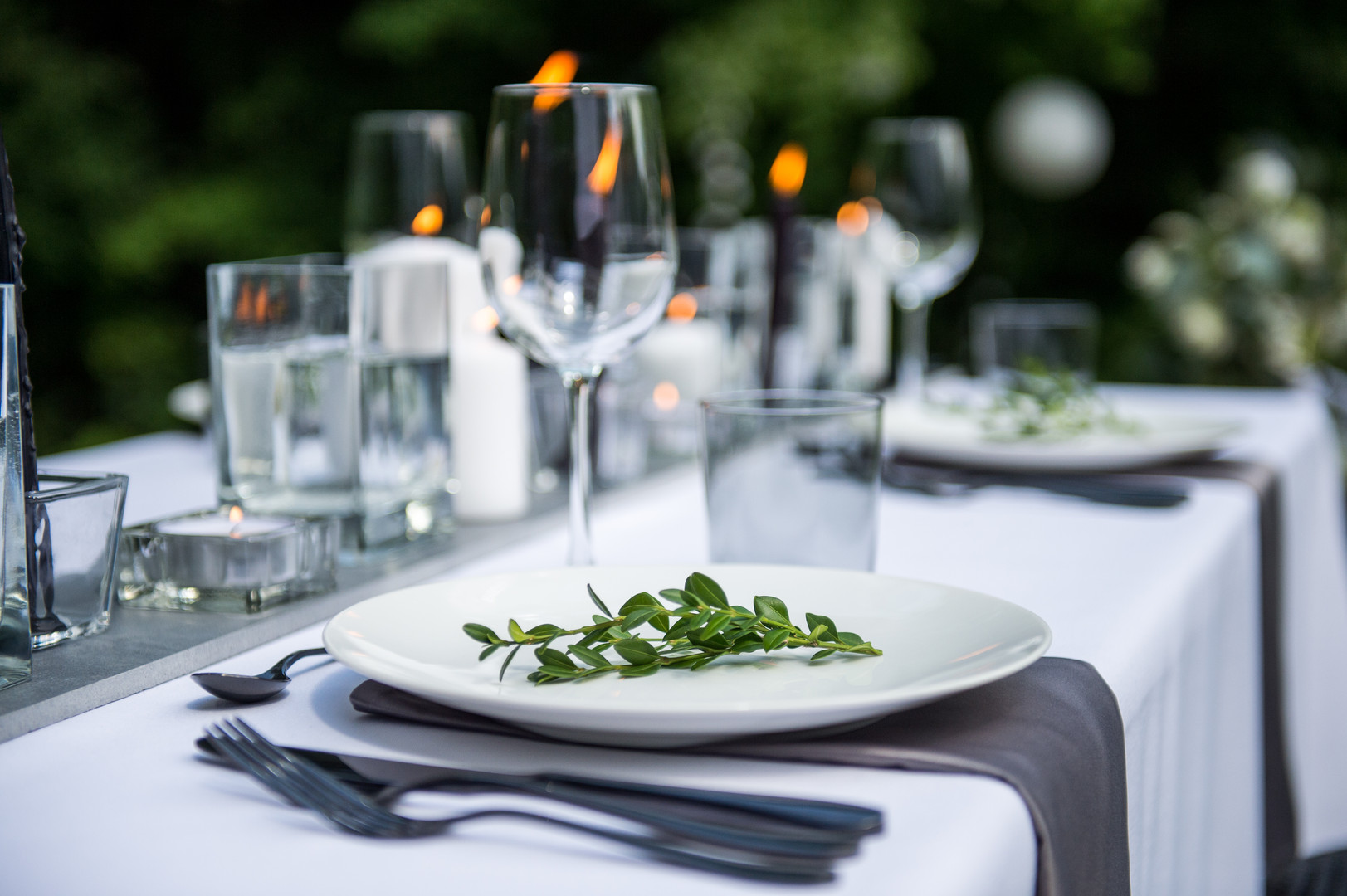 Outdoor summer wedding reception place setting with candles