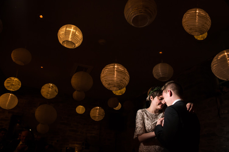 Bride and groom first dance under the ceiling lanterns
