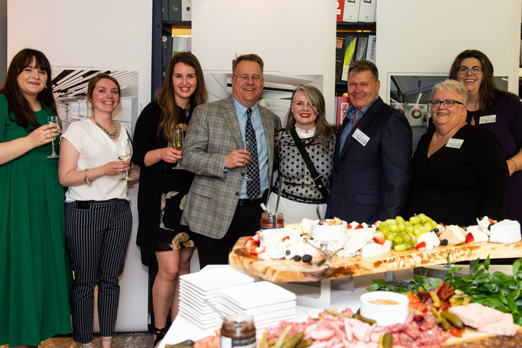 Corporate party guests with banner background and food station