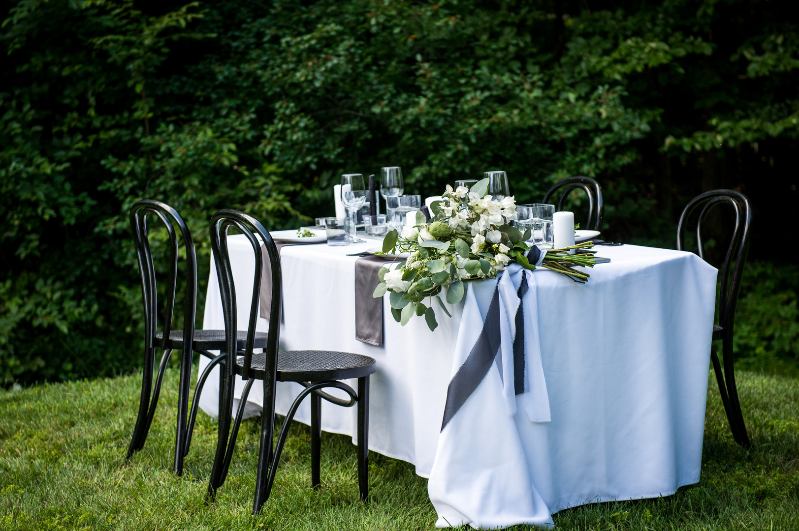 Outdoor wedding reception table with bride's bouquet