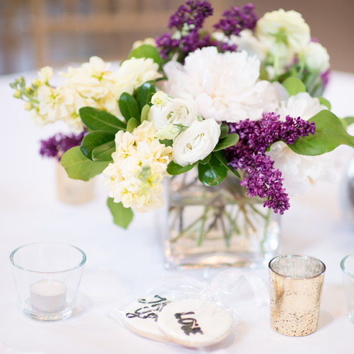 Wedding reception table centrepiece with lilacs and peonies