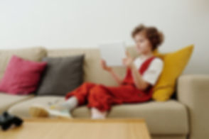 photo-of-child-sitting-on-couch-while-ho