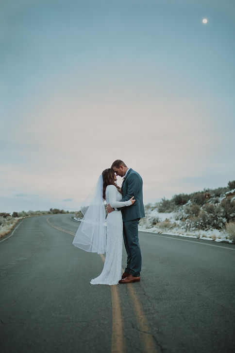 Bridal pictue at Antelope Island of bride and groom holding each other in the middle of the road with moon in the background