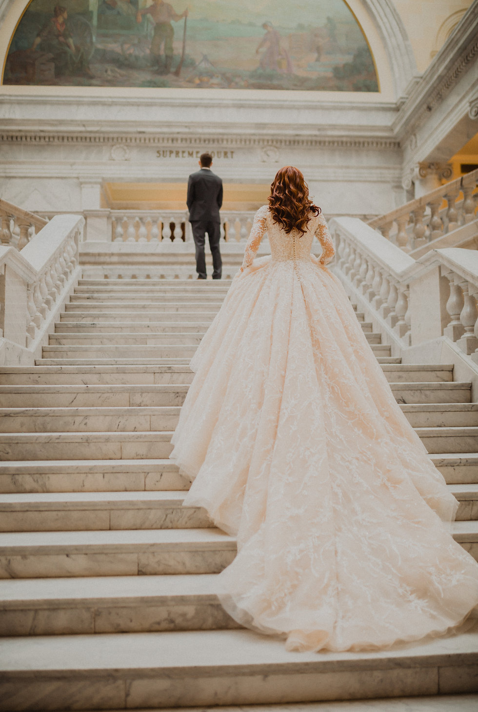 Bridal photo of bride walking up stairs in long wedding dress with groom waiting at the top of the stairs