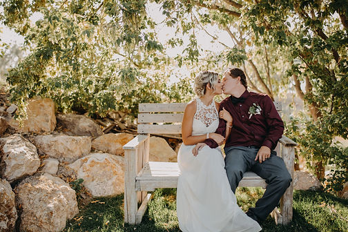 Chelsea Jessop photography Natural light bridal photo couple kissing on bench with sun behind