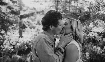 Chelsea Jessop photography; natural light engagement photo of couple kissing in forrest with sun rays