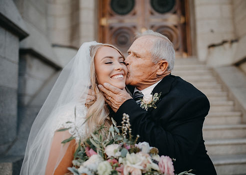 natural light wedding day photo of grandpa kissing the bride