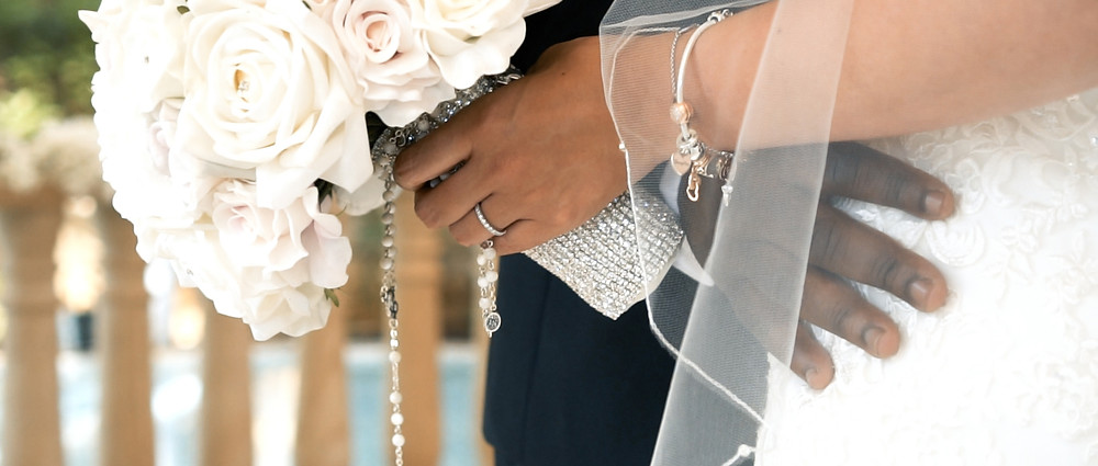 Wedding ring, hands and bouquet