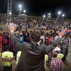 The back of Patrick Kucera withhis arms up above the crowd in a grey suit in Africa