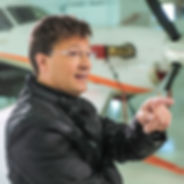 Patrick Kucera PK pointing at some cool aviation technology in a black jacket in front of planes
