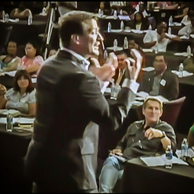 a poor picture of Patrick Kucera Speaking at a conference of people talking with his hands