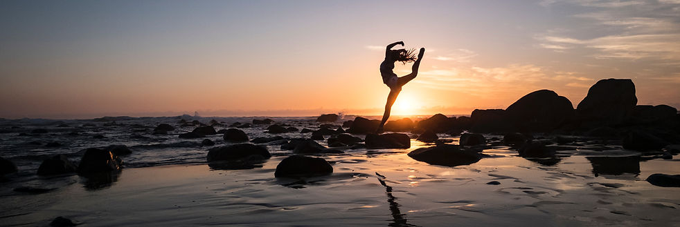 Silhouette of woman in dancers pose at sunset on the beach. Photo by Andrew Rice on Unsplash