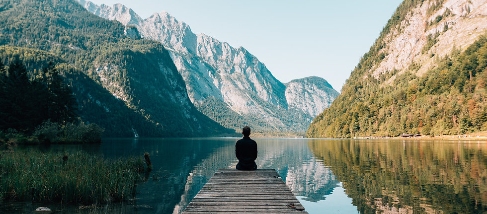 Silhoutte of a man sitting at the end of a pier looking out onto the lake and mountains. Photo by Simon Migaj on Unsplash