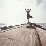 Figure at the end of a pier in a yoga pose. Photo by Marion Michele Unsplash