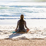 Figure in a seated yoga pose on the beach. Photo by Simon Rae Unsplash