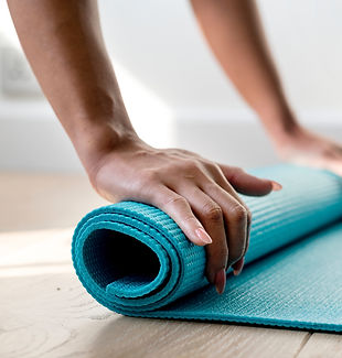 Lady's hands rolling out an aqua yoga mat. Photo by Rawpixel Unsplash