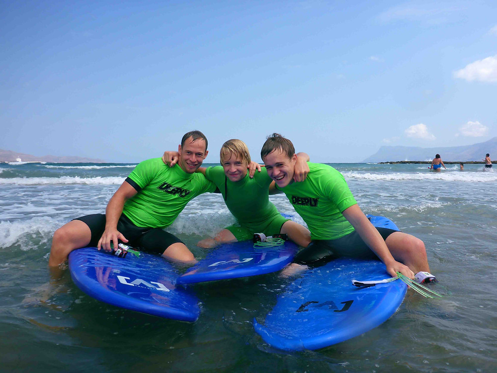 Three brothers sitting on surfboards