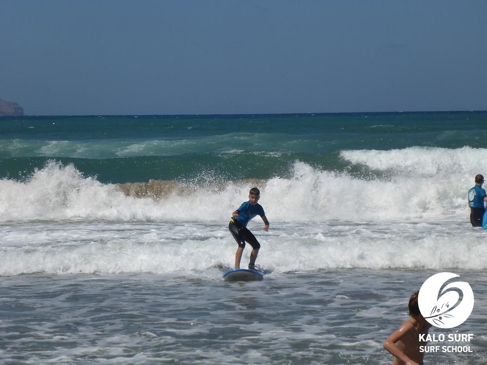 kid surfer surfing a wave in Crete