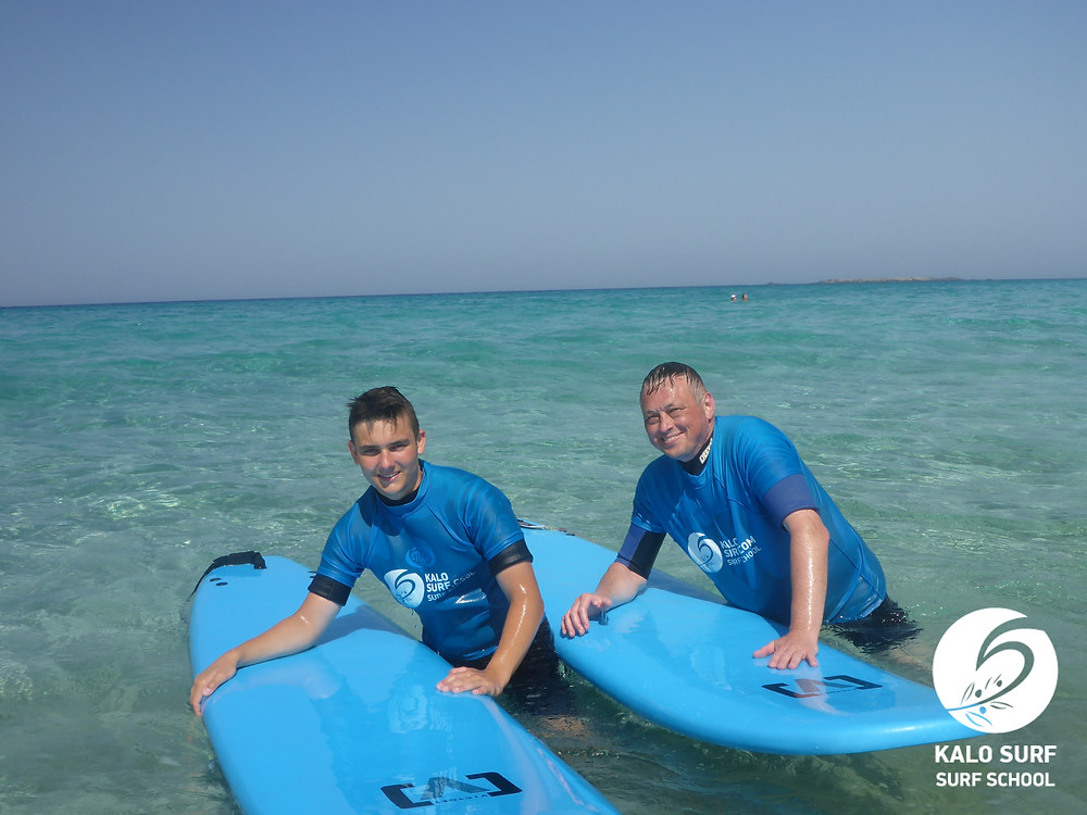 father and sun enjoy a surf lesson together in Crete