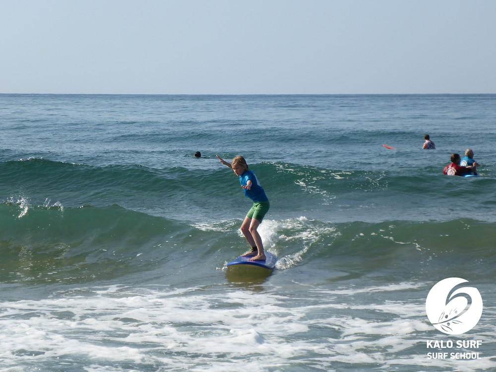 young surfer riding wave in Crete