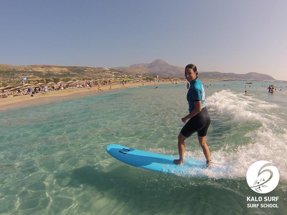 Surferin reitet eine Welle in Falassarna, Kreta