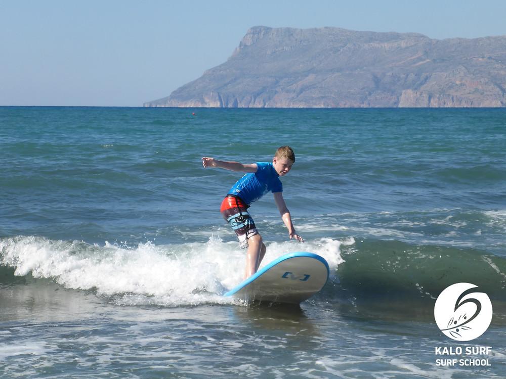 kid surfer surfing a wave on a surfboard in Crete