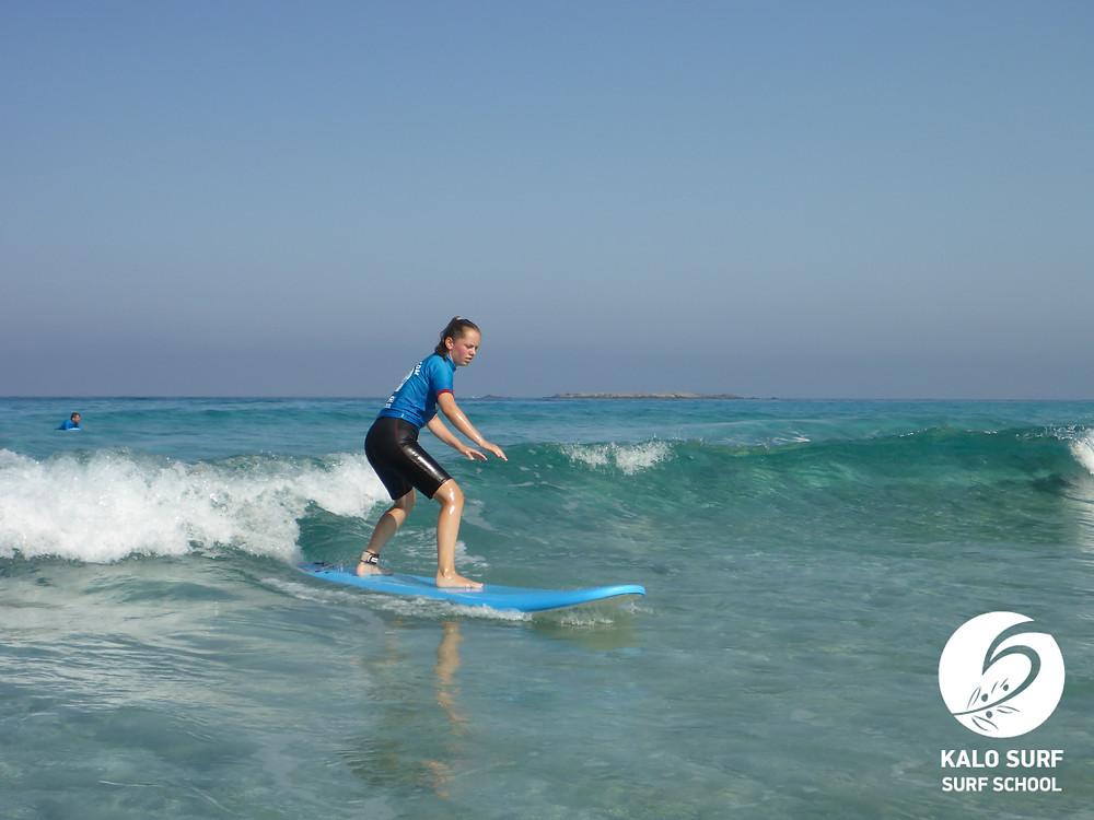 Surferin surft grüne Welle ab auf Kreta, Griechenland