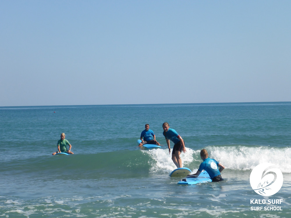 Surfer catching wave while her family looks on