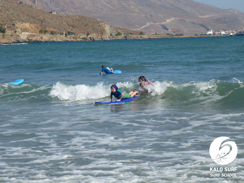 girl surfer catching a wave with the surf instructor