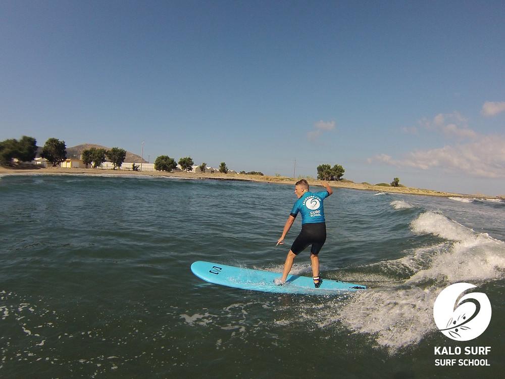 Surfschüler surft eine Welle am Riffbreak in Kreta