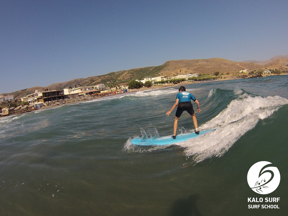 Surfer riding a wave in Crete
