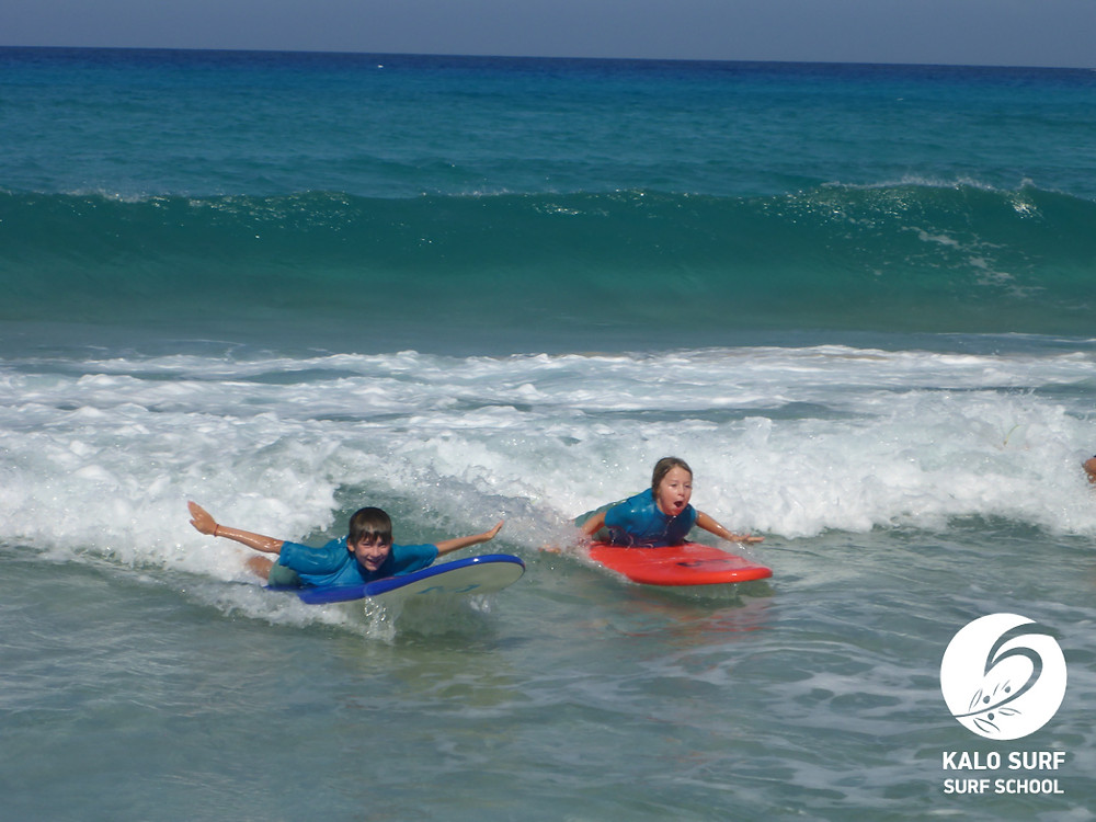 kids gliding on a wave with a surfboard in Greece