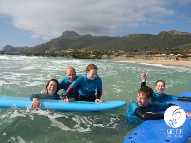 Family laughing beginner surf lesson Crete Greece