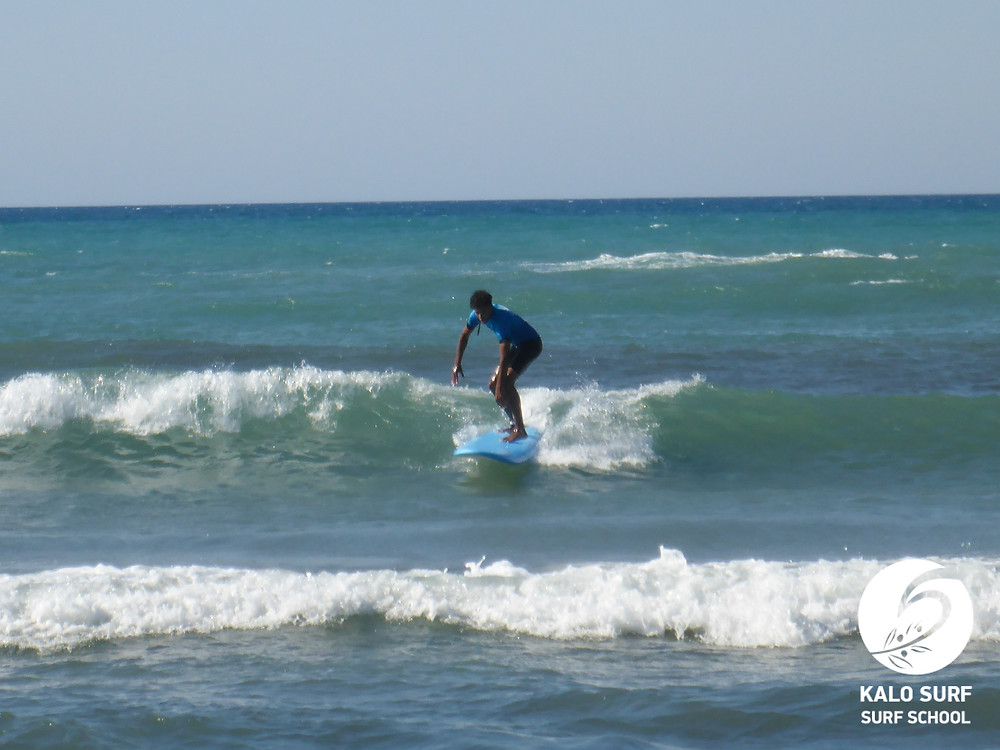 surfer taking off on a green wave in Crete